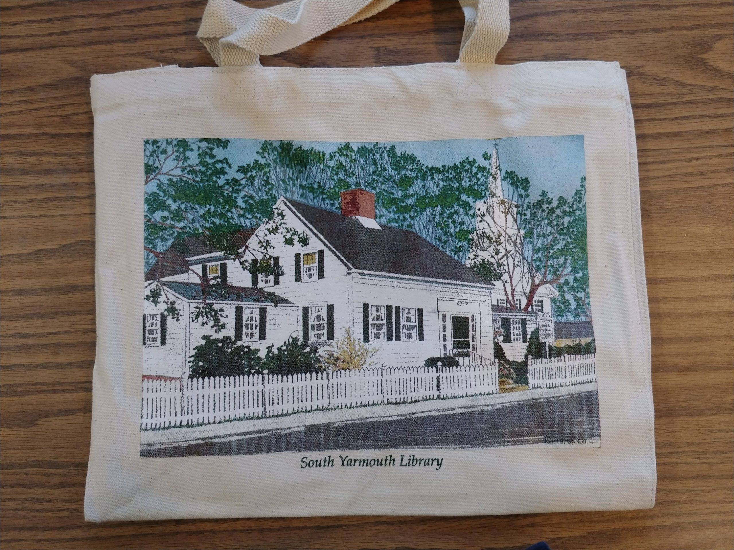Tote Bags with a screenprint image by local artist, Karol Wyckoff, of the South Yarmouth Library building.